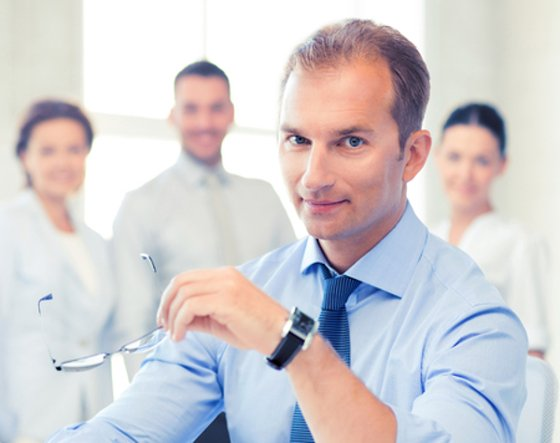 Businessman holding glasses and looking straight at the camera